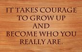 It takes courage to grow up and become who you really are - quote by E.E. Cummings on wooden red oak background