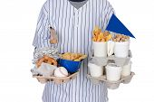 Closeup of a sports fan carrying souvenirs and food trays in both hands. Food tray had hot dogs, peanut,s pretzels, chips and french fries. Souvenirs include pennant, baseball, mini bats and helmet.