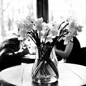 Table in the cafe with lent lily and loving couple at background. Date. Urban lifestyle. Black and w