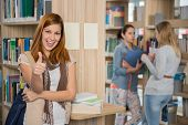 Happy student showing thumb up with friends in college library