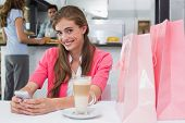 Smiling young woman using mobile phone in the coffee shop
