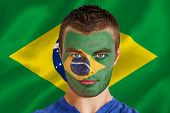Composite image of serious young brasil fan with facepaint against digitally generated brazilian national flag