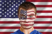 Composite image of serious young usa fan with facepaint against digitally generated american national flag