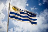 Uruguay national flag against bright blue sky with clouds