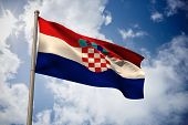 Croatia national flag against bright blue sky with clouds