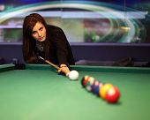 Young brunette girl playing snooker