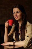 Portrait of happy brunette drinking a cup of coffee