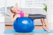 Slim blonde doing sit ups on exercise ball smiling at camera at home in the living room