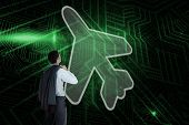 Composite image of airplane and businessman looking against green and black circuit board