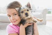 Smiling little girl holding her yorkshire terrier puppy at home in the living room