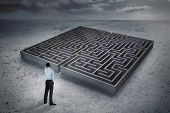 Thoughtful businessman with hand on head against big maze under cloudy sky
