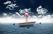 Attractive businesswoman holding red umbrella against sharks circling small boat in the sea
