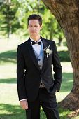 Portrait of confident bridegroom in tuxedo standing at garden