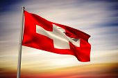 Swiss national flag against blue cloudy sky