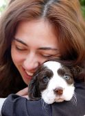 stock photo of puppy dog face  - Happy girl holding her puppy - JPG