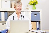 Elderly female doctor sitting smiling at laptop computer in her office