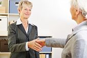 Two elderly women shaking hands after meeting in the office