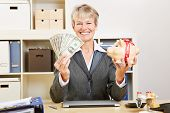 Smiling happy elderly business woman with dollar bills and a piggy bank