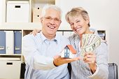 Happy elderly senior couple with small house and fan of dollar bills