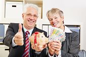 Two happy senior people with money and piggy bank holding thumb up