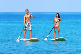 stock photo of stand up  - Stand up paddleboarding beach people on stand up paddle board - JPG