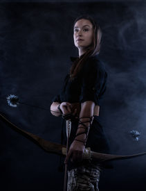image of fletching  - Beautiful archery woman and smoky blue background - JPG