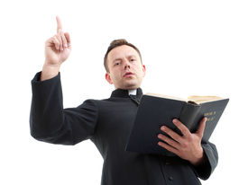picture of priest  - Catholic priest preaching while holding a Bible - JPG