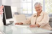 Happy elderly lady sitting at table at home, using computer, smiling at camera.