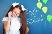 Cute girl standing near blackboard in classroom