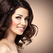 Beautiful young smiling woman with brown curly hairs looking at camera. Pretty fashion model with dark eye makeup