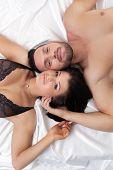 Top view of satisfied lovers posing in bed