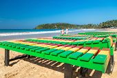 UNAWATUNA, SRI LANKA - MARCH 6, 2014: Two women walk on beach in front of colourful wooden deck chairs.  Unawatuna is a major tourist attraction in Sri Lanka famous for its beautiful beach and corals.