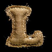 Linen or hemp vintage cloth letter L isolated on black background