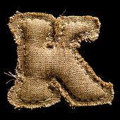 Linen or hemp vintage cloth letter K isolated on black background