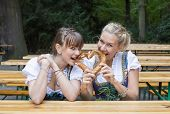Two Woman In Dirndl With Pretzel