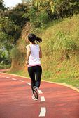 young fitness woman cross country running on mountain trail
