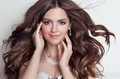 Long Blowing Hair. Beautiful Brunette Girl Model With Makeup, Fashion Jewelry, Wavy Hairstyle.