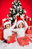 little girls twins dressed as Santa Claus with gifts
