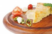 dairy food : cheese casserole triangle served on wood plate with tomatoes, capers, and chives isolat