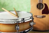 Snare Drum And Acoustic Guitar On A Green Background