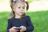 Little girl holding a smart phone and looking away.Two years.