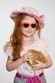 Little redhead fashionista in a sunglasses and hat. Girl is six years.