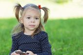 Little girl with a smartphone in the park.Two years.