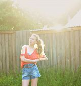portrait photo of beautiful girl in summer light standing near fence