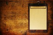 Grungy clipboard on old wooden surface, with plenty of copy space.