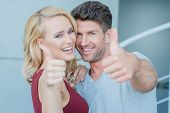 Happy laughing couple giving a thumbs up gesture of approval and success as they stand close together arm in arm with focus to their faces