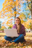 Pretty friendly woman sitting cross-legged on the ground amongst colorful leaves in an autumn park w