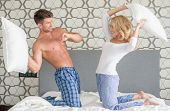 image of pillow-fight  - Playful attractive young couple having a pillow fight as they kneel on their bed in their sleepwear smiling and laughing - JPG