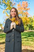 image of overcoats  - Fashionable young woman in a warm overcoat enjoying an autumn walk in a park holding a bunch of yellow leaves in her hand as she smiles at the camera - JPG