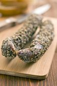 dried sausage with peppercorn on wooden table